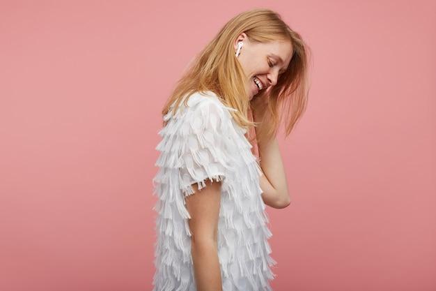 Vista lateral de uma jovem ruiva alegre com penteado casual, ouvindo música em fones de ouvido e sorrindo positivamente, vestida com uma blusa elegante branca em pé sobre um fundo rosa