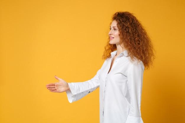 Vista lateral de uma jovem ruiva em uma camisa branca casual posando isolada em uma parede amarelo-laranja