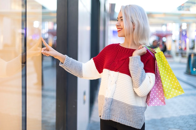 Vista lateral de uma jovem sorridente em pé em um shopping center