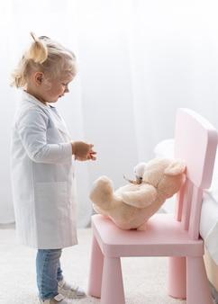 Vista lateral de uma linda criança com jaleco e ursinho de pelúcia