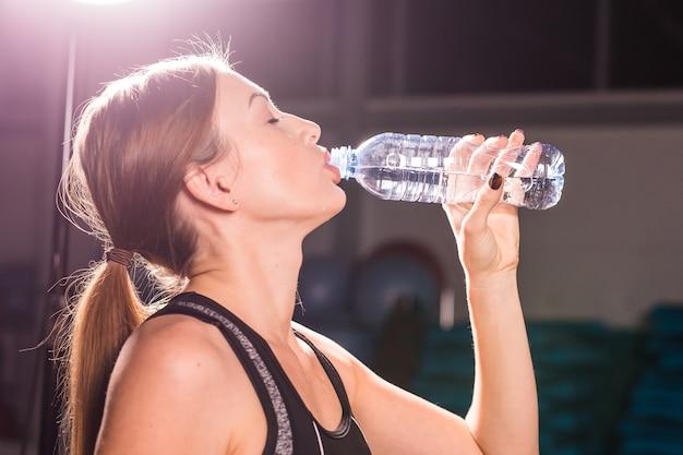 Vista lateral de uma linda garota com roupas esportivas, bebendo água após o treino no ginásio