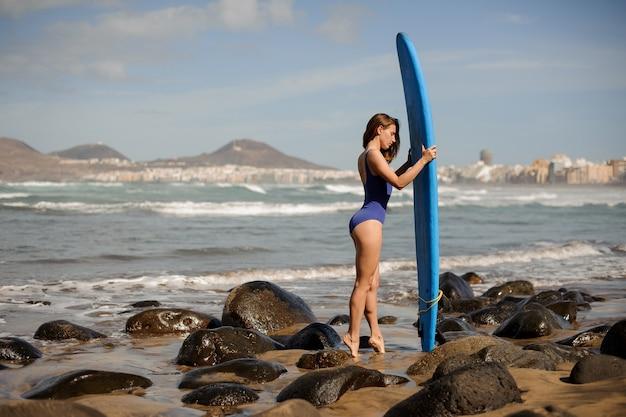 Vista lateral de uma linda garota de maiô azul em pé com a prancha de surf sobre o oceano atlântico