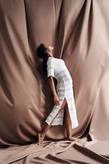 Vista lateral de uma linda garota em um vestido de renda dobrado para trás