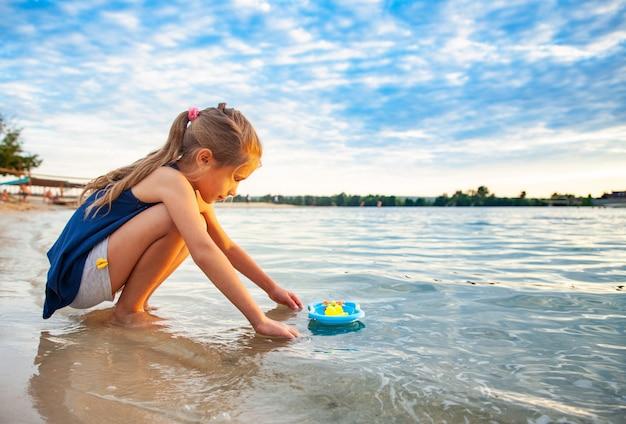 Vista lateral de uma linda menina caucasiana brincando com pequenos patos amarelos de borracha
