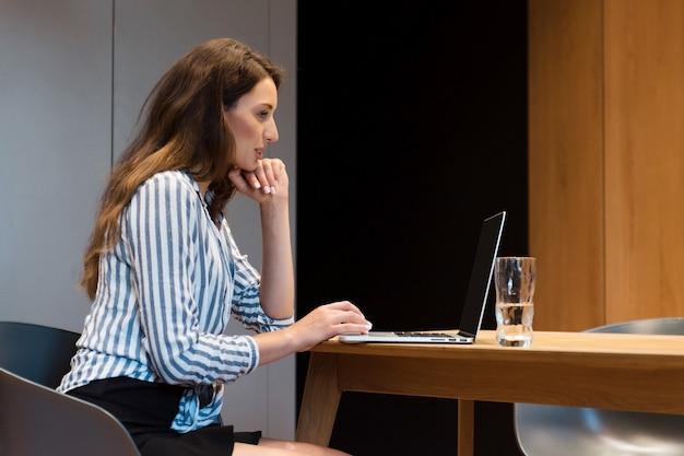 Vista lateral de uma linda mulher com longos cabelos escuros sentada à mesa e usando o computador portátil para trabalhar