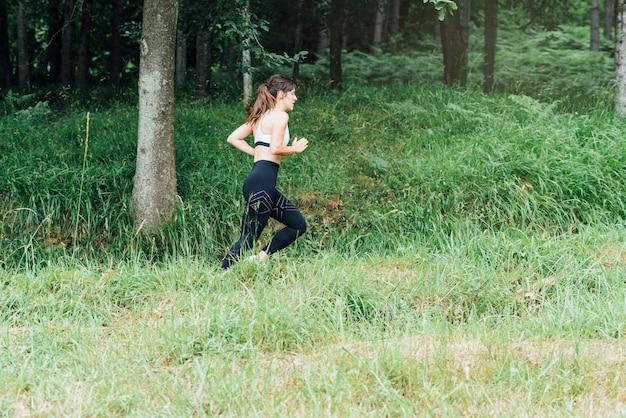 Vista lateral de uma linda mulher correndo pela floresta verde com muitas árvores