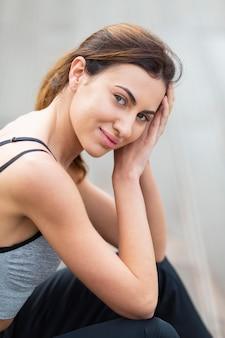 Vista lateral de uma linda mulher posando enquanto se exercita ao ar livre