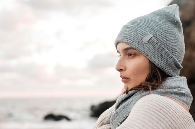 Vista lateral de uma linda mulher posando na praia com espaço de cópia