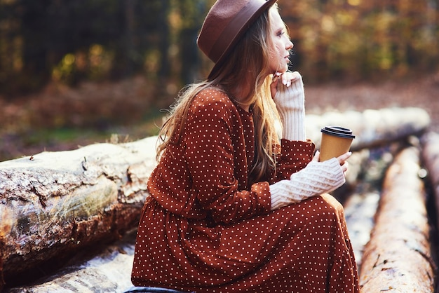 Vista lateral de uma linda mulher tomando café na floresta de outono