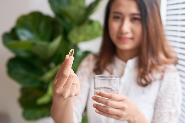 Vista lateral de uma linda mulher tomando cápsula de vitamina com um copo de água isolado no branco