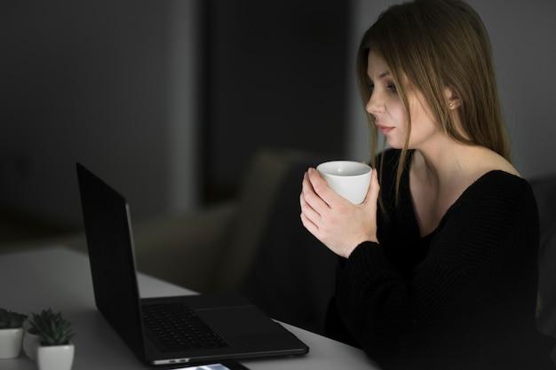 Vista lateral de uma linda mulher trabalhando na mesa