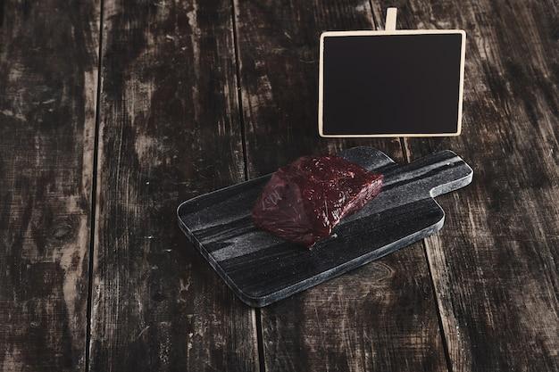 Vista lateral de uma luxuosa peça crua de bife de baleia na mesa de corte de pedra de mármore preto e mesa de madeira vintage envelhecida e etiqueta de preço do quadro de giz