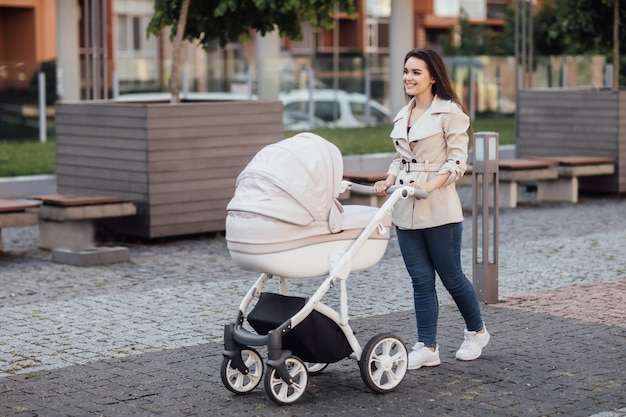 Vista lateral de uma mãe caucasiana caminhando na rua da cidade enquanto empurra seu filho sentado em um carrinho de bebê