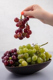 Vista lateral de uma mão feminina segurando um cacho de uva vermelha com uma tigela de uvas na superfície cinza e fundo branco