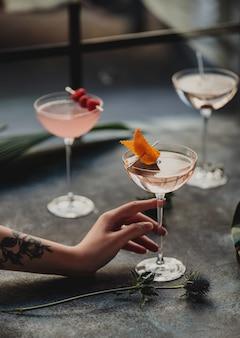 Vista lateral de uma mão feminina segurando um copo com coquetel de pin
