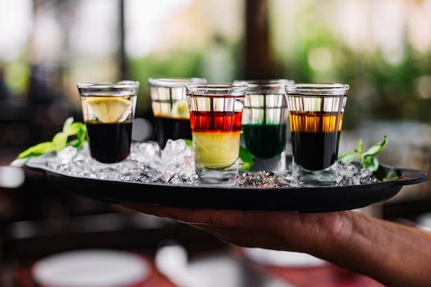 Vista lateral de uma mão segurando uma bandeja com gelo e cocktails coloridos em copos de shot