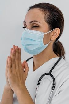 Vista lateral de uma médica rezando