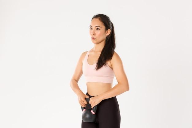 Vista lateral de uma menina asiática forte focada realizar agachamentos com kettlebell, controlar a respiração durante os exercícios de fitness, fazer exercícios de reabilitação.