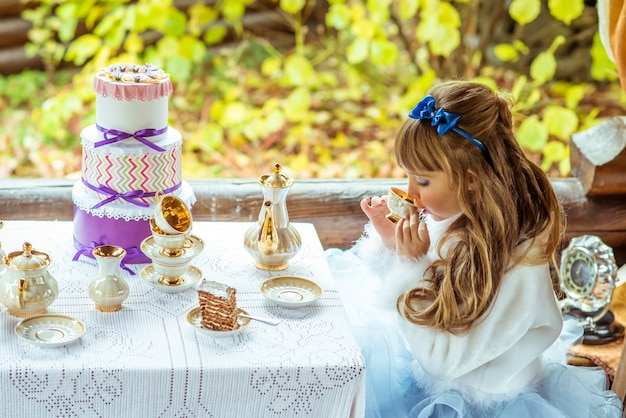 Vista lateral de uma menina bonita no cenário, bebendo um chá na mesa do parque