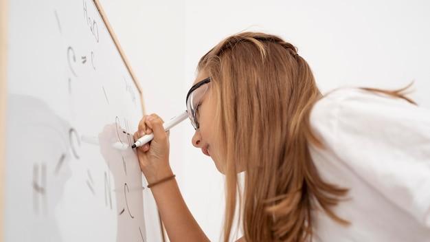 Vista lateral de uma menina escrevendo no quadro branco enquanto aprende ciências