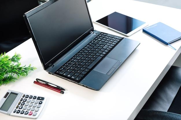 Vista lateral de uma mesa de escritório com um laptop, calculadora, notebook, tablet, canetas com fundo branco e luz muito boa
