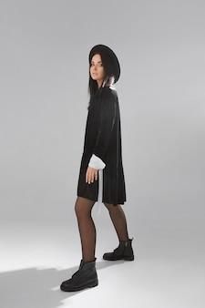 Vista lateral de uma modelo mulher em um vestido preto curto e chapéu preto sobre fundo branco em estúdio de alta qualidade. cosplay de fotos de bruxa para o halloween