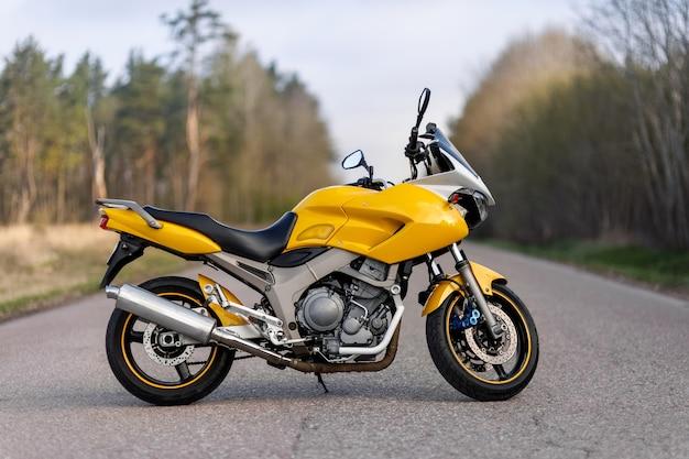 Vista lateral de uma motocicleta amarela em uma estrada em uma área florestal