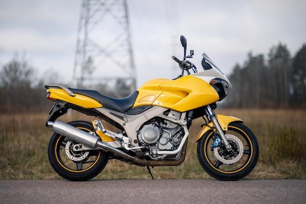 Vista lateral de uma motocicleta amarela na beira de uma estrada