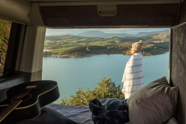 Vista lateral de uma mulher admirando a natureza durante uma viagem