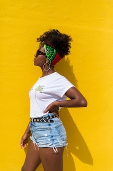 Vista lateral de uma mulher afro com óculos escuros e lenço na cabeça, encostado na parede amarela enquanto olhando para longe
