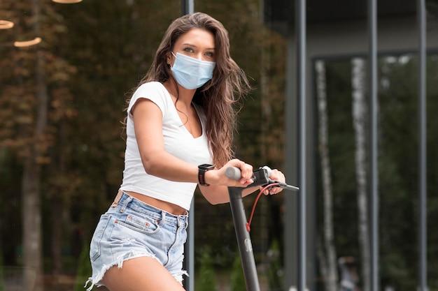 Vista lateral de uma mulher andando de scooter elétrica com máscara médica