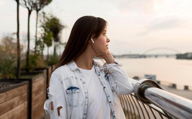 Vista lateral de uma mulher ao ar livre curtindo música nos fones de ouvido