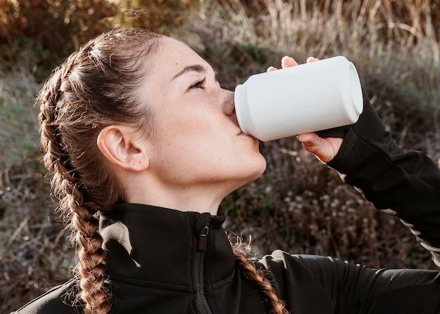 Vista lateral de uma mulher atlética bebendo refrigerante