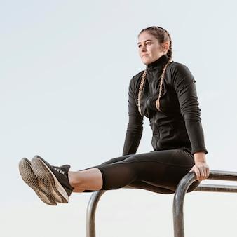 Vista lateral de uma mulher atlética fazendo exercícios ao ar livre