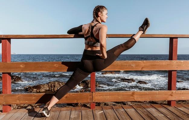 Vista lateral de uma mulher atlética se alongando na praia