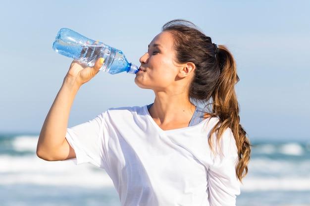 Vista lateral de uma mulher bebendo água na praia após malhar