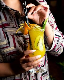 Vista lateral de uma mulher bebendo citsu cocktail com fatias de limão e kiwi, decorado com casca de laranja em vidro