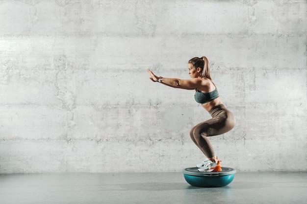 Vista lateral de uma mulher caucasiana muscular em roupas esportivas e com rabo de cavalo, fazendo resistência de agachamento na bola de bosu.