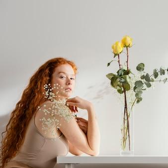 Vista lateral de uma mulher com flores da primavera em um vaso sobre a mesa