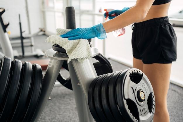 Vista lateral de uma mulher com luvas, desinfetando equipamentos de ginástica