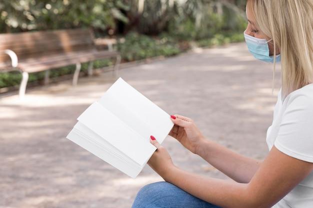 Vista lateral de uma mulher com máscara médica lendo um livro enquanto está sentada no banco