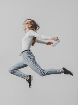 Vista lateral de uma mulher com máscara médica pulando no ar