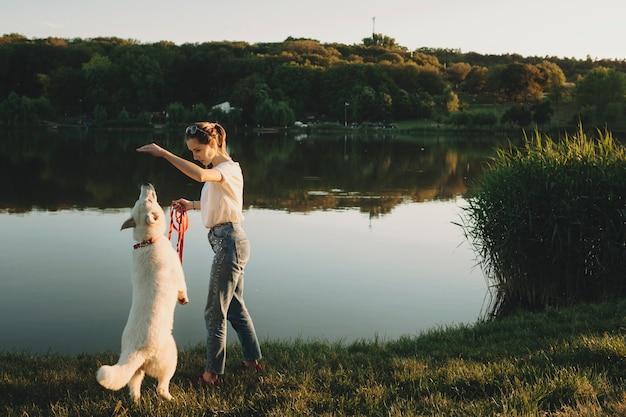 Vista lateral de uma mulher com roupas de verão, segurando a mão e brincando com um cachorro branco nas patas traseiras ao pôr do sol com água e árvores no fundo