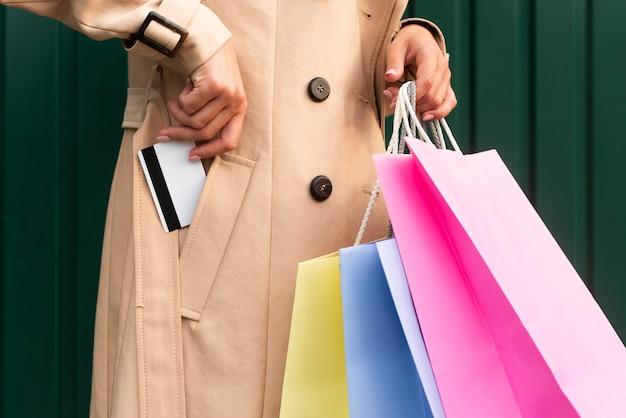 Vista lateral de uma mulher com sacolas de compras, colocando o cartão de crédito no bolso