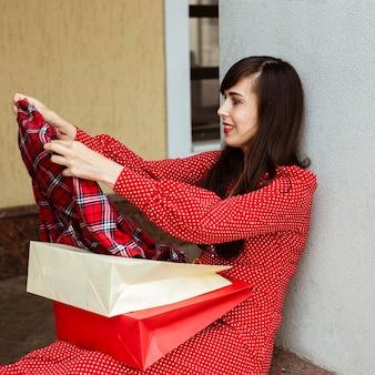 Vista lateral de uma mulher com sacolas de compras e roupas à venda