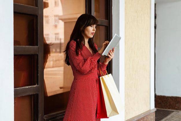 Vista lateral de uma mulher com sacolas de compras usando o tablet para vendas