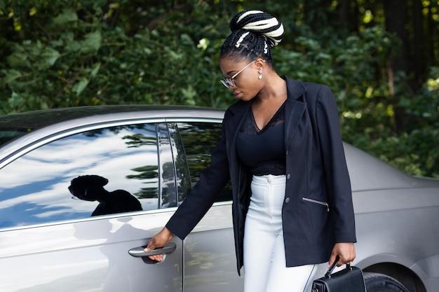 Vista lateral de uma mulher com uma bolsa abrindo a porta do carro