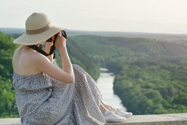 Vista lateral de uma mulher com uma câmera fotográfica. vista de uma colina em uma floresta verde e rio