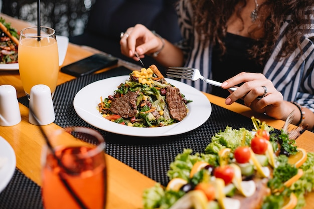Vista lateral de uma mulher comendo salada de carne com legumes e grãos
