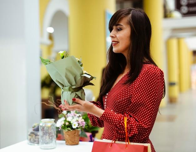 Vista lateral de uma mulher comprando uma planta enquanto segura sacolas de compras